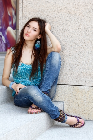Outdoors portrait of beautiful young sad teen girl sitting on stairs  photo