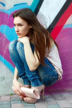 Outdoors portrait of beautiful fashion girl sitting near wall with abstract graffiti photo