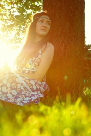 mujeres tristes: Al aire libre Retrato de muchacha joven hermosa que se sienta en la hierba bajo el �rbol Foto de archivo