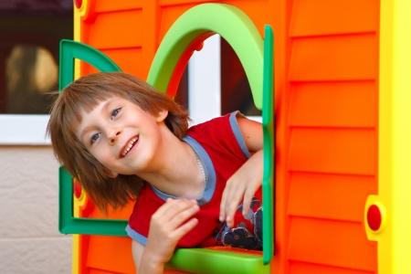bambini pensierosi: Carino felice ragazzo sorridente che gioca in casa giocattolo sul campo da giuoco, estate parco