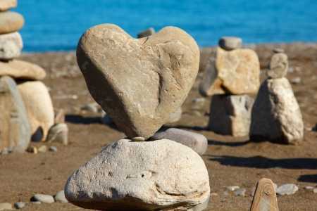 heart of stone: group of balanced stones with rocks heart at front view, pebbles stacks against blue sea Stock Photo