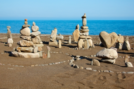 art therapy: group of balanced stones with rocks heart at front view, pebbles stacks against blue sea Stock Photo