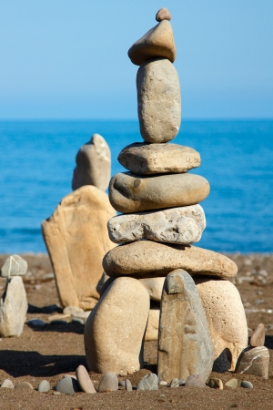 art therapy: balanced stones, pebbles stacks against blue sea Stock Photo