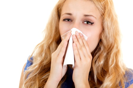 blows: Young woman with cold sneezing into tissue over white background  Stock Photo