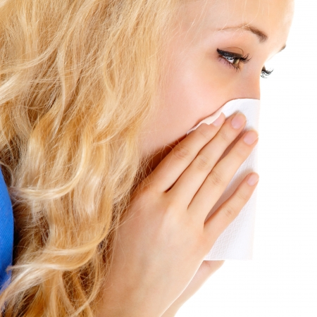 Young woman with cold sneezing into tissue over white background  photo