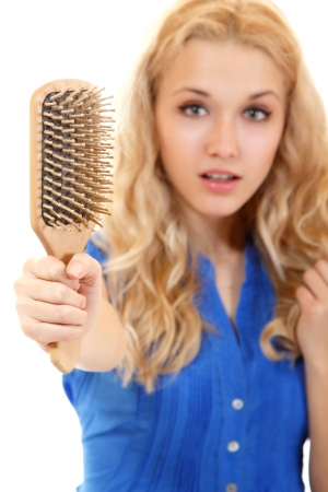 pelade: women with hair broblem holding loss hair comb in hand, isloated on white background Stock Photo