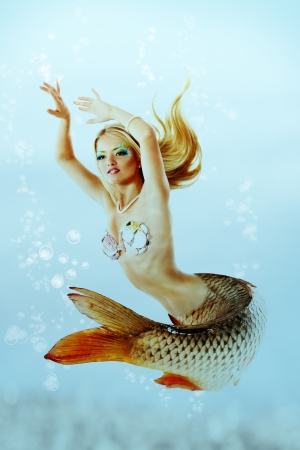 portrait of beautiful mermaid girl with fish tail and long blond hair swimming in ocean magic mythology being original photo compilation  photo