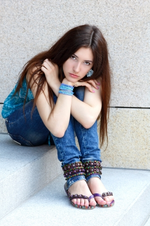 cute teen girl: Outdoors portrait of beautiful young sad teen girl sitting on stairs