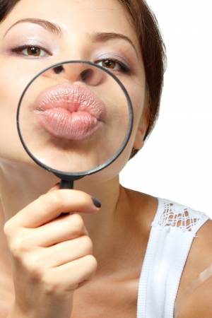 sexy kiss: Smiling attractive give kiss through a magnifying glass over white background