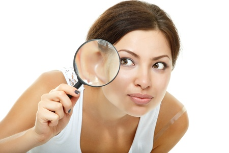 sleuth: Attractive woman looking through a magnifying glass over white background Stock Photo