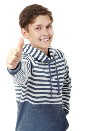 Cheerful attractive teen boy thumb up over white background photo