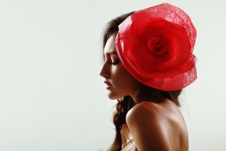 Vintage portrait of fashion glamour girl with red flower in her hair. Studio shot. photo
