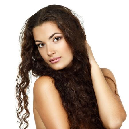 hair curly: Retrato de la belleza de la hermosa mujer joven alegre con dulce largo marrón pelo rizado saludable. Aislado sobre fondo blanco
