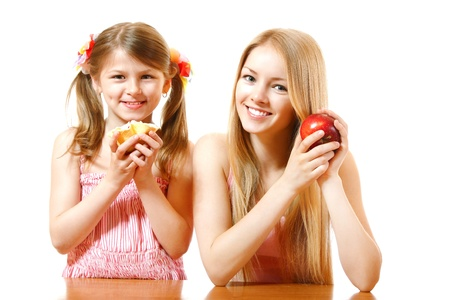teeny: happy teeny girl with red apple and little girl with cake, isolated on white background Stock Photo
