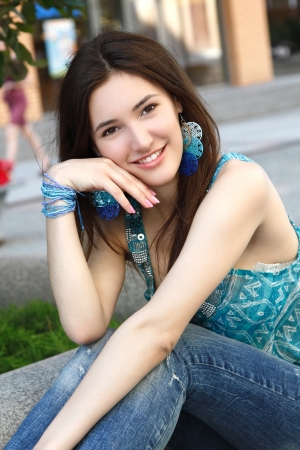 Outdoors street portrait of beautiful young brunette teen girl photo