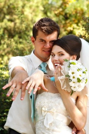 beautiful young bride and groom show their wedding rings in love outdoor Stock Photo - 16694139