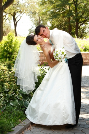 beautiful happy young bride and groom hug in love summer park outdoor photo