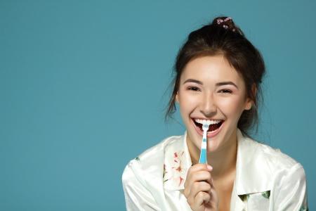 healthy teeth: Chica adolescente feliz divertido cepillarse los dientes. Ma�ana tema. Sobre fondo azul.