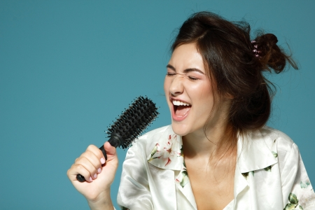 Cheerful attractive teen girl sing song holding comb like a microphone in the morning. Over blue background. photo