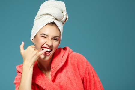 bath gown: Cheerful attractive funny teen girl clean her teeth in the morning. Over blue background.