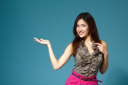 beautiful teen girl showing something with hand, over blue background Stock Photo - 16694148