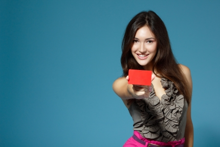 beautiful teen girl showing red card in hand, over blue background Stock Photo - 16761744