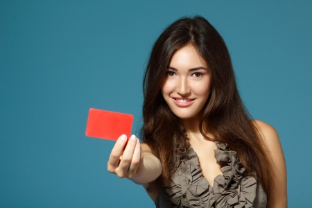 beautiful teen girl showing red card in hand, over blue background Stock Photo - 16694225