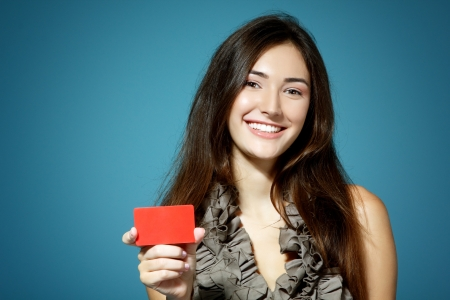 beautiful friendly smiling confident girl showing red card in hand, over blue background photo