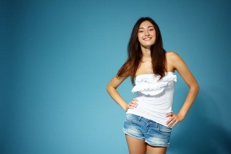 top: beautiful teen girl in jean shorts and white top over blue background