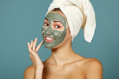 pamper: Spa teen girl applying facial clay mask. Beauty treatments. Over blue background.
