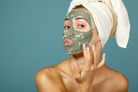 Spa teen girl applying facial clay mask. Beauty treatments. Over blue background. photo