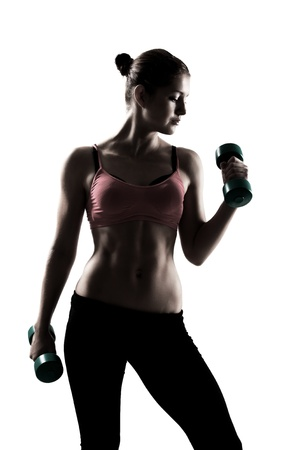 mujeres fitness: muchacha deportiva que hace ejercicio con pesas, silueta tiro del estudio sobre fondo blanco