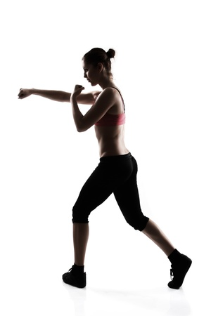 martial arts: sporty young woman doing martial arts exercise, silhouette studio shot over white background Stock Photo