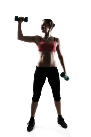 sporty girl with dumbbells, silhouette studio shot over white background photo