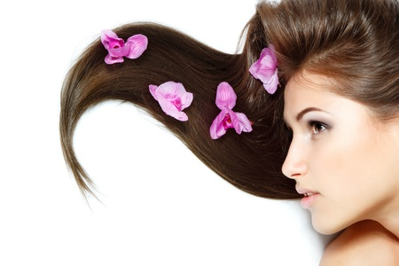 beauty girl, happy young natural beautiful woman over white background with long brown hair and purple orchid, over white background photo
