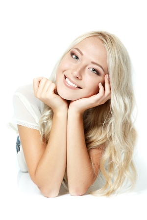 teen girls: Beautiful blond teen girl lying, looking at camera and happy smiling. Isolated on white background