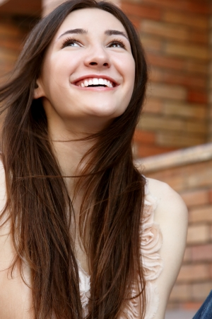 pretty teen girl: Outdoors street portrait of beautiful young brunette happy smiling teen girl