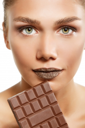 sexual pleasure: young fresh beautiful woman eating chocolate, beauty female face portrait isolated on white background