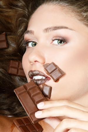 melt chocolate: joven mujer hermosa que come el chocolate dulce, retrato belleza rostro femenino aislado sobre fondo blanco