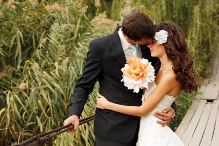 vőlegény: fiatal esküvői pár, gyönyörű menyasszony goom portréja a hídon, nyári szabadtéri Stock fotó