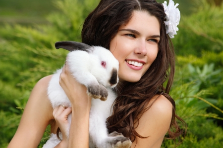 Young beautiful girl smiling and holding cute rabbit over park summer nature outdoor, Alice in Wonderland