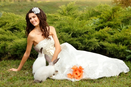 Young woman bride smiling playing with cute rabbit over park summer nature outdoor, Alice in Wonderland Stock Photo - 16764713