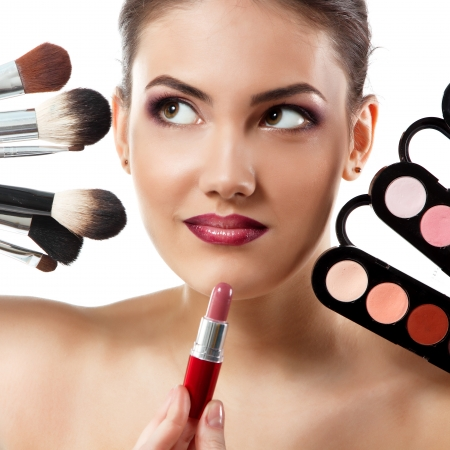 beauty portrait of young beautiful woman with makeup brushes, lipstick and palette of eye shadows isolated on white background photo