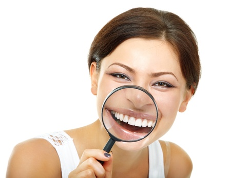 funny woman smiling and show teeth through a magnifying glass over white background photo