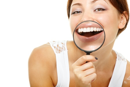 big teeth: funny woman smiling and show teeth through a magnifying glass over white background
