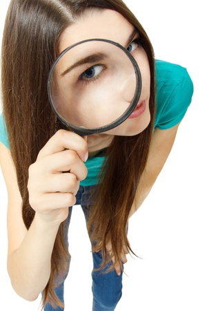 Attraktive Mädchen schaut durch ein Vergrößerungsglas über weißem Hintergrund
