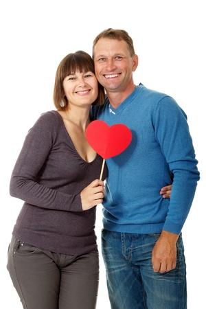man vrouw symbool: Aantrekkelijke vrolijke vrouw met de mens in liefde glimlachend over witte achtergrond. Portret van gelukkige volwassen vrouw hugs haar man met rood hart, geïsoleerd