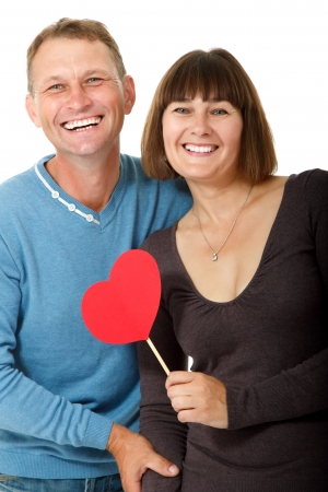 Attractive cheerful woman with man in love smiling over white background. Portrait of happy mature wife hugs her husband with red heart, isolated Stock Photo - 16764590