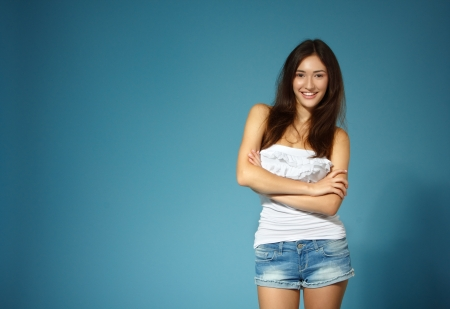 beautiful cheerful teen girl in jean shorts and white top over blue background photo