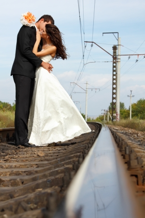 beautiful young couple bride with groom in love on railway, summertime photo